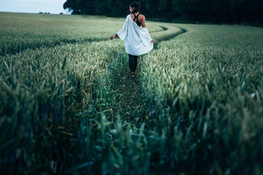 Modern Mystery School woman walking through a field with a path
