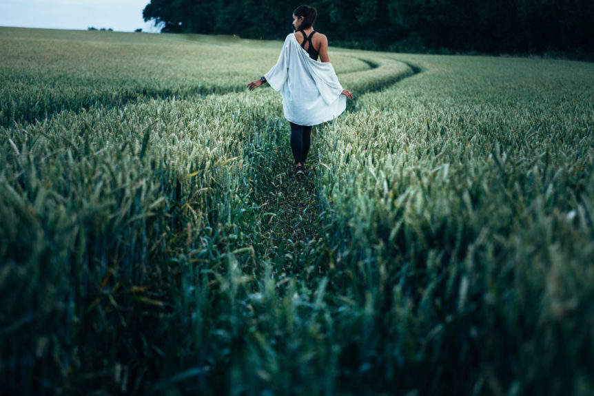 Modern Mystery School woman walking through a field with a path